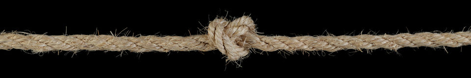 Long rope tied in a knot. Isolated on black Royalty Free Stock Photo