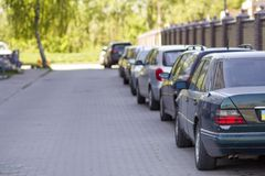 Long row of cars parked in quiet neighborhood on clean empty pav. Ed street along new stone fence on background of beautiful green trees on bright sunny summer Royalty Free Stock Images