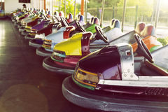 Long row of colorful bumper cars parked in an amusement park. Vintage effect with lens flare Royalty Free Stock Photography