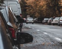 Long row of different shiny cars and vans parked along empty roadside on sunny autumn day on blurred green golden stock photos
