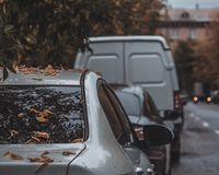 Long row of different shiny cars and vans parked along empty roadside on sunny autumn day on blurred green golden foliage bokeh royalty free stock images