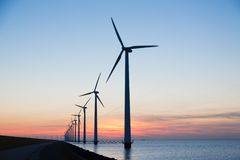 Long row of wind turbines with sunset over the sea Royalty Free Stock Photography