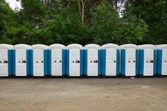 Toilets installed at a public event. Long row of mobile toilets stock images