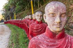 Buddhist monks stone statues row at Kaw Ka Thaung cave, Hpa-an, Myanmar. Long row of monk statues at Kaw Ka Thaung cave stock photos