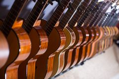 Line of new acoustic guitars in store. Long row of new acoustic guitars in store Royalty Free Stock Images