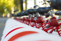Long row of public hire bicycles with selected focus on one of the bikes Stock Images