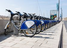 A long row of rental bikes. A long row of rental bicycles with royal blue and white fenders and orange reflectors. Banners and pale blue sky are in the Stock Photo