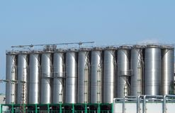 Long row of stainless storage silos for liquids and differents types of free flowing raw materials stock photography