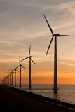 Long row of windturbines in the sea royalty free stock images