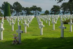 Long rows of white crosses at the Normandy American Cemetery and Memorial, Normandy, France with the sea in the background. Endless lines of white crosses at the stock photography