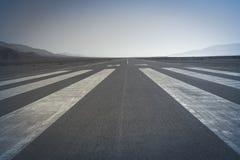 Long runway. Long paved runway shot from its threshold markings royalty free stock image