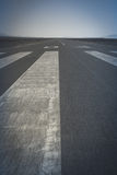 Long runway. Long paved runway shot from its threshold markings Royalty Free Stock Photos