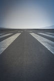 Long runway. Long paved runway shot from its threshold markings Stock Images