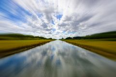 Long rural canal. Long canal along a rural area on a cloudy day with a blurred effect royalty free stock photos