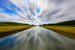 Long rural canal. Long canal along a rural area on a cloudy day with motion blur effect stock images