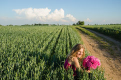 Long rural path and woman sits with peony flower Royalty Free Stock Photography