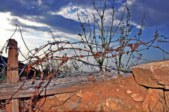 Long rusted barbed wire barrier at the end of the road under cloudy sky Stock Image