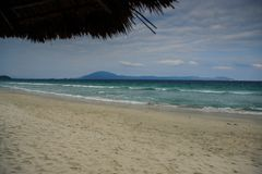 Long Sand Beach with Azure Sea Waves Surf against Blue Sky Stock Photo