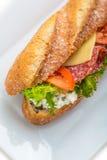 Long sandwich avec du jambon, le fromage, les tomates et la laitue Sur le fond blanc Image stock