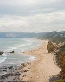 Long sandy beach with cliffs and gentle waves. Aerial view looking down a long sandy beach with tall cliffs and gentle waves. people walking along beach Royalty Free Stock Photo
