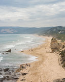 Long sandy beach with cliffs and gentle waves. Aerial view looking down a long sandy beach with tall cliffs and gentle waves. people walking along beach Royalty Free Stock Photography
