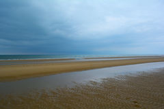 Long sandy beach of Norfolk coast and low dark blue cloudy sky, Northern Sea, Holkham beach, United Kingdom royalty free stock photography