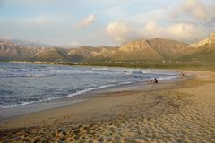 Long sandy beach at sunset in the south of the island of Mallorca. View of the long sandy beach at sunset with mountains on background. This view taken in the Royalty Free Stock Photo