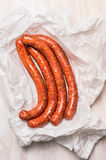 Long sausage meat in white wrapping paper on wooden  background, top view Stock Photos