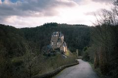 Long scenic road leading to a beautiful castle. Fabulous medieval place in the forest. Sunny rays pipes out from clouds. Traveling in Europe stock photography
