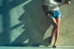 Long sexy leg women jeans shorts fashion standing to wall Stock Photography