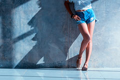 Long sexy leg women jeans shorts fashion standing to wall Royalty Free Stock Image