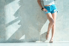 Long sexy leg women jeans shorts fashion standing to wall Royalty Free Stock Images