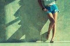 Long sexy leg women jeans shorts fashion standing to wall Stock Photo
