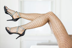 Long and sexy legs in elegant high heels and fishnet stockings Royalty Free Stock Photo