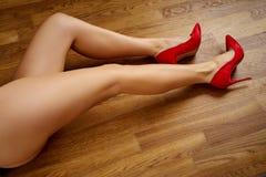 Long woman`s legs in red high heels on wooden floor. Long woman`s legs in red high heels on wooden oak floor stock photo