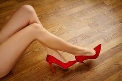 Long woman`s legs in red high heels on wooden floor. Long woman`s legs in red high heels on wooden oak floor stock photos