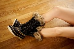 Long woman`s legs in warm snow boots on wooden floor. Long woman`s legs in warm snow boots on wooden oak floor stock photos
