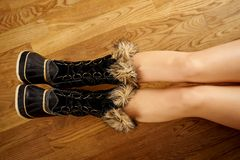 Long woman`s legs in warm snow boots on wooden floor. Long woman`s legs in warm snow boots on wooden oak floor royalty free stock photos