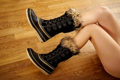 Long woman`s legs in warm snow boots on wooden floor. Long woman`s legs in warm snow boots on wooden oak floor royalty free stock photography