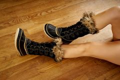 Long woman`s legs in warm snow boots on wooden floor. Long woman`s legs in warm snow boots on wooden oak floor royalty free stock images