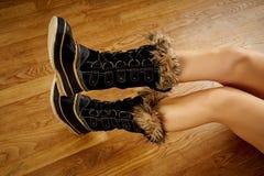 Long woman`s legs in warm snow boots on wooden floor. Long woman`s legs in warm snow boots on wooden oak floor stock photo