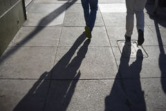 Long shadow of people walking on street Stock Photography