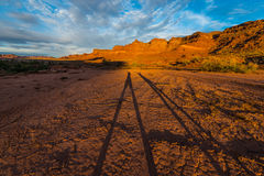 Long Shadow of two happy hikers raising their hands Sunset in th. Shadow of two happy hikers White Canyon Lake Powell at Sunset Royalty Free Stock Photos