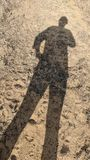 Long shadow of a woman outside. In the dirt royalty free stock image