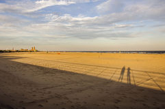 Long Shadows on the Beach. Setting sun casts long shadows on the People Beach at Jacob Riis Park in Queens, New York Stock Photo