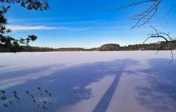 Long shadows on the lake. Winter landscape royalty free stock photo