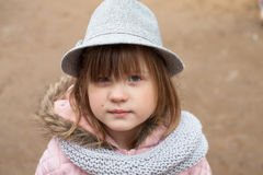Long shaggy girl in jacket, gray scarf and fedora hat Stock Image