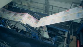 Newspaper sheets moving on a conveyor, close up. Long sheets on a conveyor stock video
