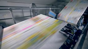 Long sheets of newspaper on a print office line, close up. Sheets moving on a special line