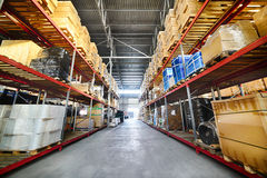 Long shelves with a variety of boxes and containers. Commercial warehouse. Long shelves with a variety of boxes and containers Royalty Free Stock Image